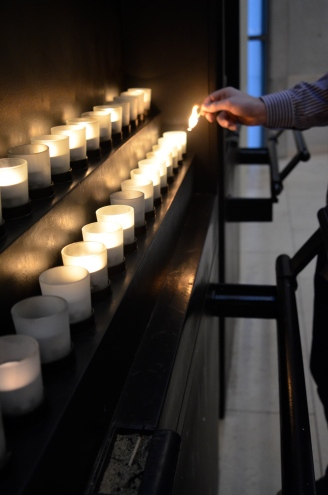 Nate Erickson lights a candle in honor of the Holocaust victims at the end of the exhibit.