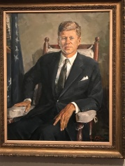President John F. Kennedy seated. (Photo Credit: Riley Fink)